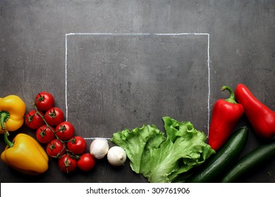 Fresh vegetables with chalk frame on grey kitchen table