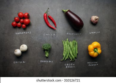 Fresh vegetables with chalky signs on grey kitchen table