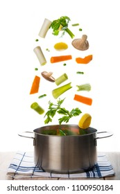 Fresh vegetables to cook a soup falling into a pot isolated on a white background