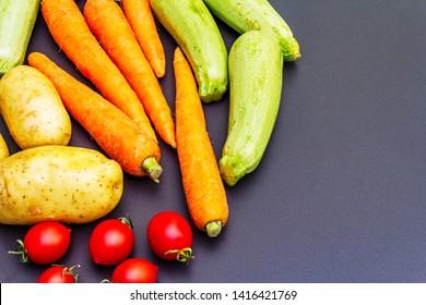 Fresh vegetables cooking black stone background. Organic ingredients for cooking stews, roasting and other healthy vegetarian (vegan) food