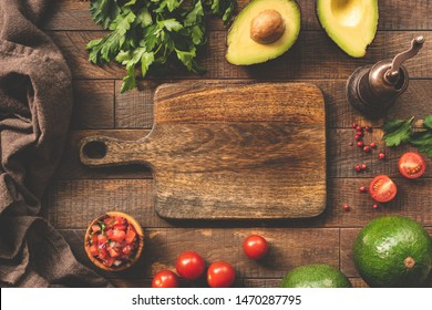 Fresh vegetables and cutting board for cooking, food frame background. Avocado, tomato, salsa, parsley and pepper spices on wooden table