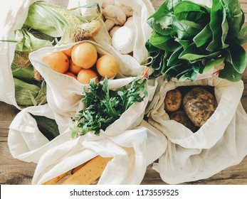 fresh vegetables in eco cotton bags on table in the kitchen. lettuce, corn, potatoes, apricots, bananas, rucola, mushrooms from market. zero waste shopping concept.   ban plastic