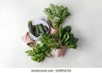 fresh vegetables in eco cotton bags, paper package on table in the kitchen. Cucumbers, salad, kale, basil, rucola from organic market. zero waste shopping concept