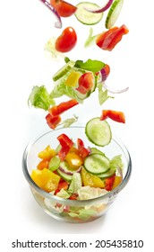 Fresh vegetables falling into the glass bowl on a white background