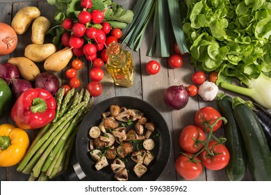 Fresh vegetables and fried mushrooms in a pan on a wooden table