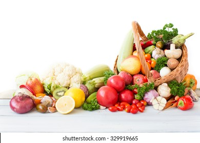 Fresh vegetables and fruit in basket on white background.