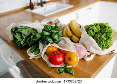 Fresh vegetables and fruits in eco cotton reusable bags on wooden table in the kitchen. zero waste shopping concept. Sustainable living
