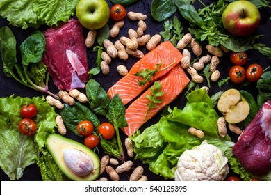 Fresh vegetables, fruits, fish, meat, nuts on black chalk board background. Cauliflower, avocado, apples, tomatoes, salmon, beef, spinach, herbs. Diet/healthy/paleo food. Ingredients for cooking