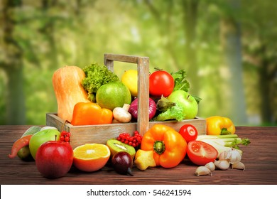 Fresh vegetables and fruits on wooden table against nature background