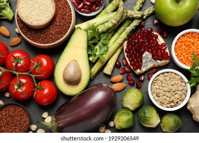 Fresh vegetables, fruits and seeds on black table, flat lay
