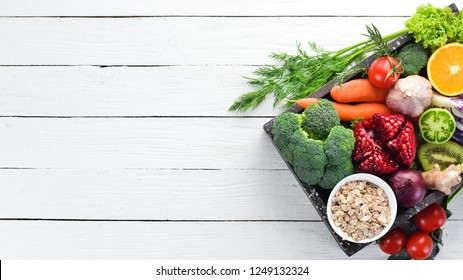 Fresh vegetables and fruits in a wooden box on a white wooden background. Organic food. Top view. Free copy space.