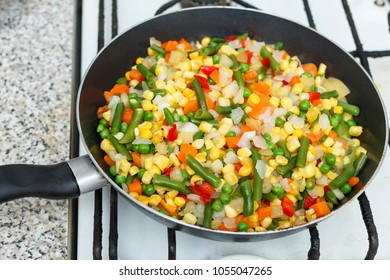 Fresh vegetables in a frying pan. Fresh vegetable products, freshly frozen odietic vegetables, broccoli, corn, asparagus, pepper, carrots are cooked in a frying pan on a gas stove.