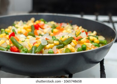 Fresh vegetables in a frying pan. Fresh vegetable products, freshly frozen odietic vegetables, corn, asparagus, pepper, carrots are cooked in a frying pan on a gas stove.