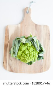 Fresh vegetables, green cauliflower on a wooden cutting board against a white background top view