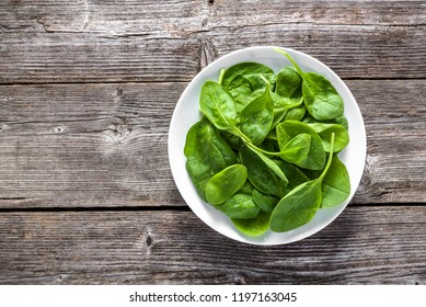 Fresh vegetables, green spinach on plate, top view on wooden table