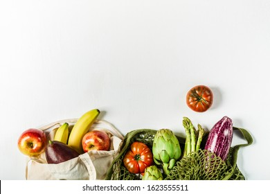 Fresh vegetables in a green string bag and fruit in a bag made of natural materials, eco-friendly product on a light gray background. No plastic.