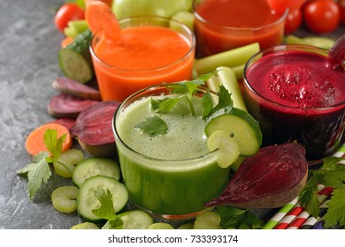 Fresh vegetables juices on a gray background
