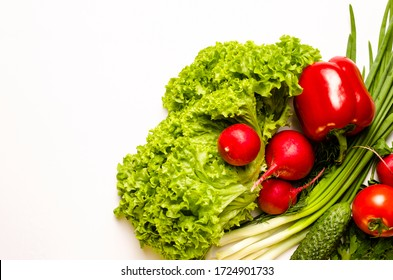 Fresh vegetables. Leaves of lettuce salad, radish, green onion, bell pepper, cucumber, parsley, dill on a white background.Vegetarian food. Place for text.Top view.