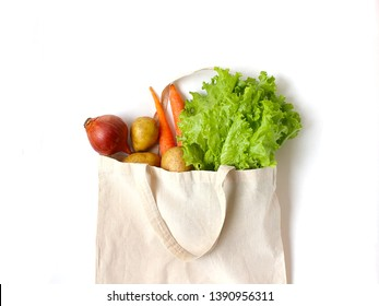 Fresh vegetables in a linen bag for shopping. ingredients for vegitarian meal. Zero waste food, eco lifestyle, No plastic living. Healthy organic vitamin  Onion, carrot, potato, salad leafes isolated