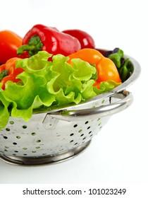 Fresh vegetables in metal colander over white