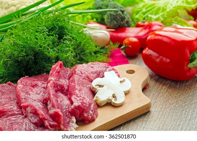 fresh vegetables, mushrooms, champignons,cabbage, pepper, cherry, greens on a wooden board with crude stakes of meat of veal, spices, close up, the top view