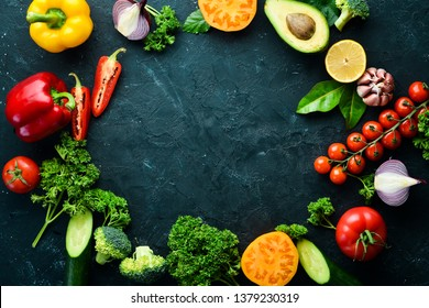 Fresh vegetables on a black background. Avocados, tomatoes, potatoes, paprika, citrus. Top view. Free space for your text.