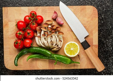 fresh vegetables on the cutting board and knife : garlic, cherry tomatoes, hot pepper, armillaria honey fungus , lemons.