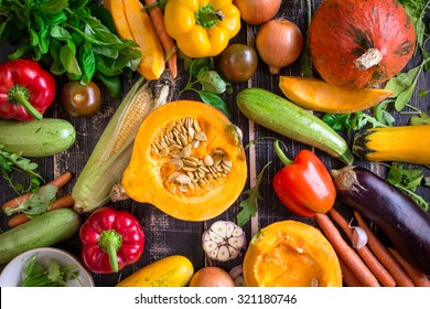 Fresh vegetables on a dark table. Autumn background. Healthy eating. Sliced pumpkin, zucchini, squash, bell peppers, carrots, onions, garlic, tomatoes, eggplant, corn cob, rucola and basil. Top view
