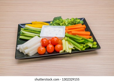 Fresh vegetables on a decorative black plate with herbal dressing