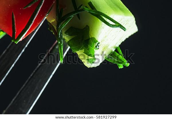 Fresh vegetables on a fork, close-up. Focus on vegetables