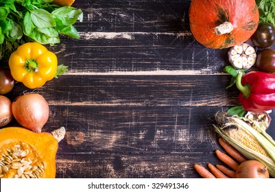 Fresh vegetables on a rustic dark textured table. Autumn background. Healthy eating frame. Sliced pumpkin, zucchini, squash, bell peppers, carrots, onions, garlic, tomatoes. Top view. Space for text