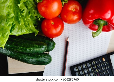 Fresh vegetables on the table: red pepper, lettuce, cucumber, tomatoes, sheet for notes - notepad. Cutting board, Food imitation. Inflation