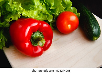 Fresh vegetables on the table: red pepper, lettuce, cucumber, tomatoes. Cutting board