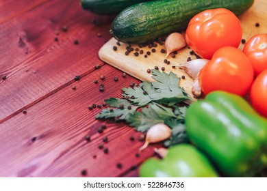 Fresh vegetables on a wooden background: tomatoes, cucumber, bell pepper, garlic, parsley, spices.