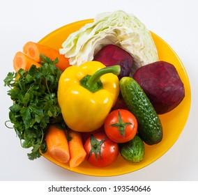 fresh vegetables in orange plate. white background