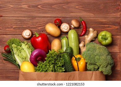 Fresh vegetables in a paper bag on a wooden table. Top view.