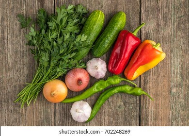 Fresh vegetables (pepper, garlic, onion, parsley) on an old wooden table, fresh food.