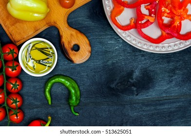 Fresh vegetables, pepper, tomato, olive oil, cooking on a dark wooden background with space for text. View from above. Bio healthy food ingredients.