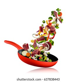 Fresh vegetables and pieces of beef meat flying into a pan, isolated on white background. Concept of flying food, preparation, diet and healthy eating.