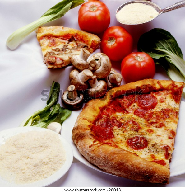 Fresh vegetables with a pizza and slices of pizza