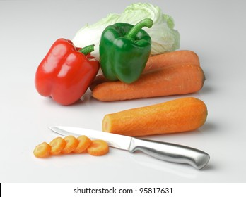 Fresh vegetables ready for cooking such as sweet pepper lettuce and carrots on grey background