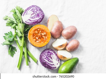 Fresh vegetables - red cabbage, potatoes, onion, celery, pumpkin and avocado on a light background, top view. Clean eating concept