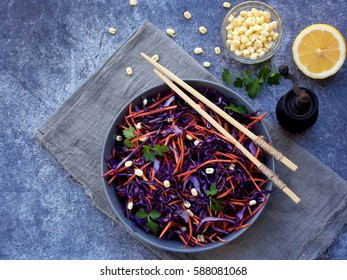 Fresh vegetables salad with purple cabbage, carrot, sprouted mung, parsley on grey clay plate on dark background. Cole Slaw Salad of red cabbage. Top view. Copy space