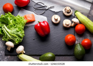 Fresh vegetables, salmon and salad on a blackboard prepared for cooking