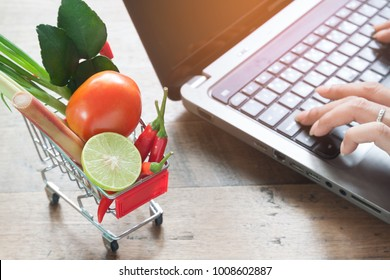 Fresh vegetables in shopping cart with woman using computer, Online shopping, Lifestyle concept
