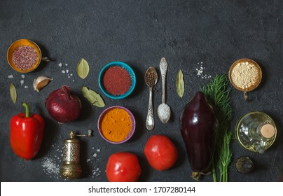 Fresh vegetables and spices in multicolored dishes on a black background, top view with space