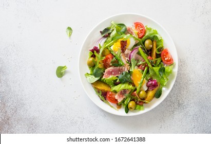 Fresh vegetables, tuna, eggs, mix salad leaveses salad  on a gray stone background. Flat lay. Copy space