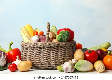 Fresh vegetables and wicker basket on white wooden table