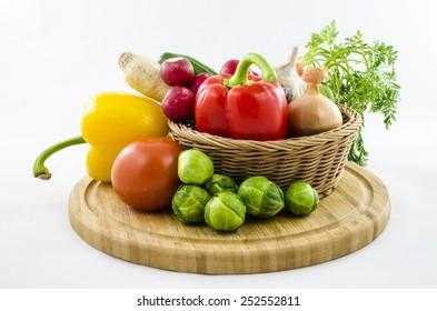 Fresh vegetables in wicker basket on wooden board.