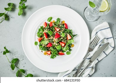 Fresh vegetarian salad with kale, strawberries, quinoa and mint leaves. White plate from above (top view, flat lay). Grey stone background.